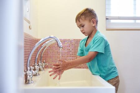 Male Pupil At Montessori School Washing Hands In Washroom