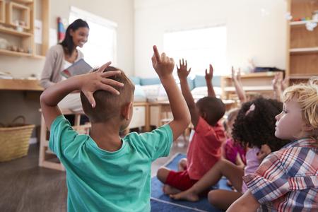 Pupils At Montessori School Raising Hands To Answer Question Foto de archivo