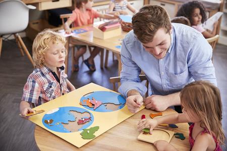 Leraar en leerlingen die houten vormen gebruiken in de school Montessori Stockfoto