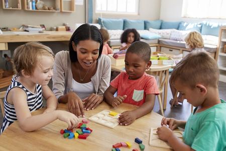 先生と生徒のモンテッソーリ学校で木製の形状を使用して