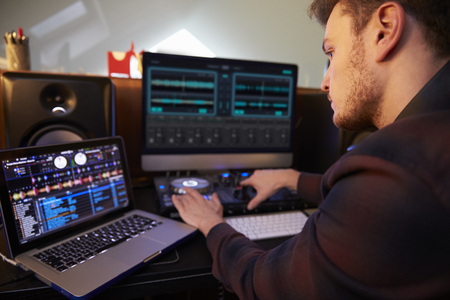 Young Man Composing Music on Laptop Computer in Bedroom