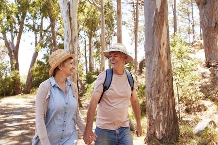 Mature Couple Hiking Along Forest Path Together Standard-Bild