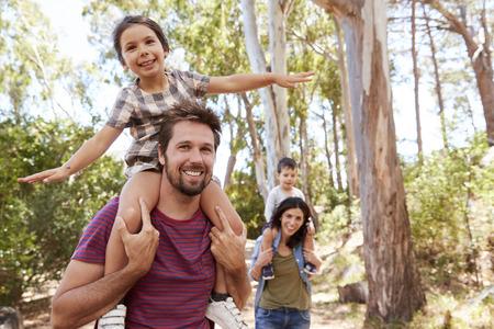시골에서 부모님의 어깨를 타고 걷는 어린이