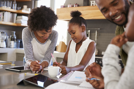 Parents Helping Children With Homework In Kitchen Stock Photo