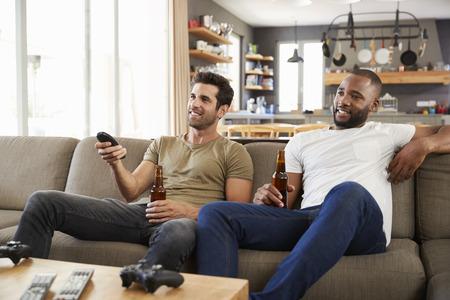 Twee mannelijke vrienden zitten op de bank en kijken naar sport op televisie Stockfoto