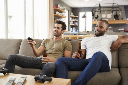 Two Male Friends Sit On Sofa And Watch Sports On Television Stock Photo
