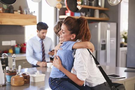 Moeder zegt vaarwel tegen de zoon als ze naar het werk vertrekt Stockfoto