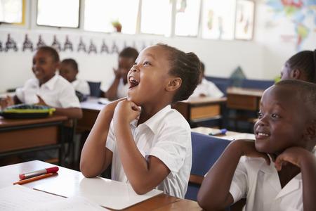 초등 학교에서 수업 중 응답하는 소녀 스톡 콘텐츠