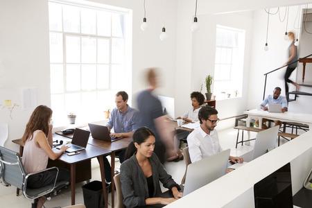 Jonge bedrijfscollega's die in een bezig open planbureau werken