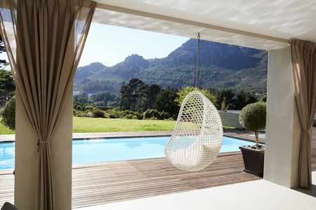 Suspended Seat Next To Decking Around Outdoor Swimming Pool Reklamní fotografie - 85280789