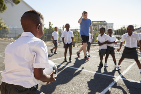 Teacher plays football with young kids in school playground Stockfoto