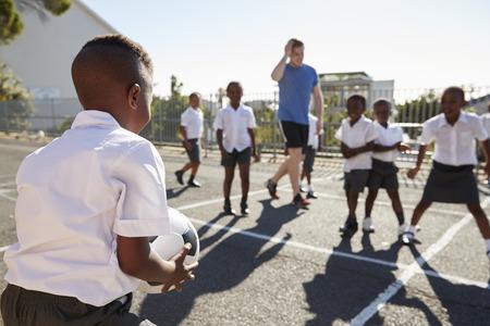 Leraar speelt voetbal met jonge kinderen op school speeltuin Stockfoto