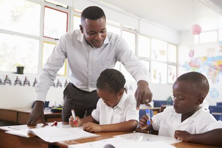 초등학생들을 도와주는 교사