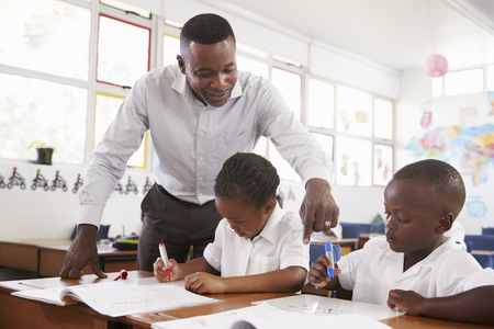 Teacher stands helping elementary school kids at their desks