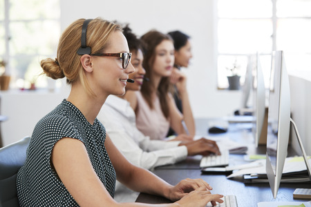 Woman with headset at computer in office beside colleagues
