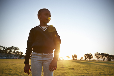 African elementary school girl in a park at sunset, close up Stock Photo