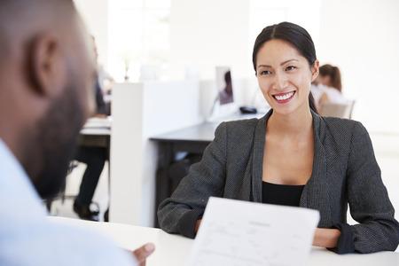Mujer sonriente hablando con un hombre en una reunión en una oficina ocupada Foto de archivo - 85280872