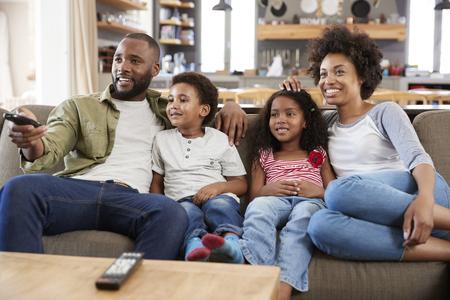 Familia sentada en el sofá en el salón de plan abierto viendo televisión Foto de archivo - 85280880
