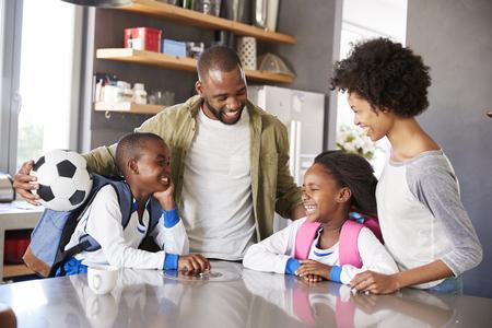 子供たちが学校へ出発するとき、子どもたちにさよならを言う両親