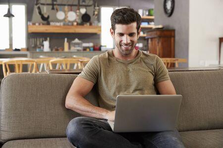 Man Sitting On Lounge Sofa Using Laptop Stock Photo