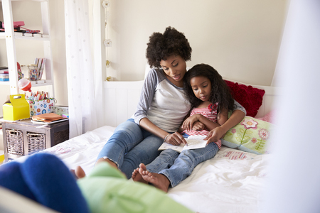 Mother And Daughter Siting On Bed Reading Book Together Stock Photo
