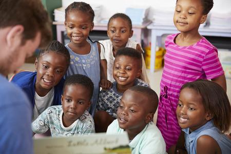 Teacher reading book to elementary school children in class