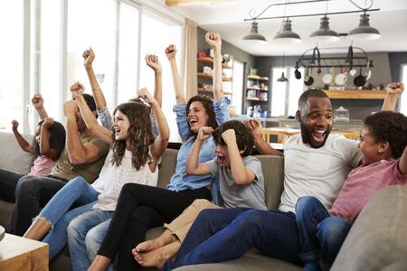 Twee gezinnen kijken naar sport op televisie en juichen