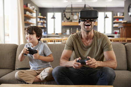 Father And Son Play Computer Game Using Virtual Reality Headset Stock Photo