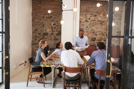 Young black man handing out paperwork at a team meeting Stock Photo