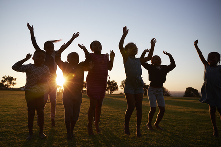 Silhouetted school kids jumping outdoors at sunset Stok Fotoğraf - 85280584