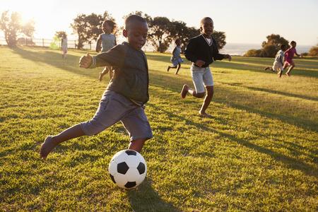 Basisschooljonge geitjes die voetbal in een gebied spelen Stockfoto