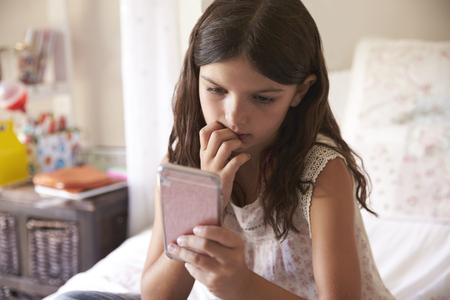 Young Girl In Bedroom Worried By Bullying Text Message Archivio Fotografico
