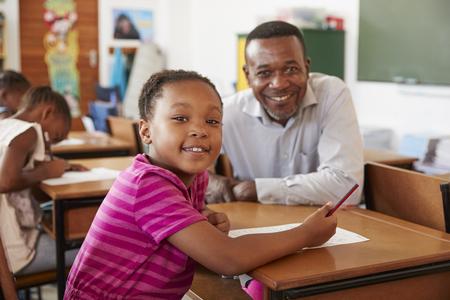 Black teacher and elementary school girl smiling to camera 写真素材