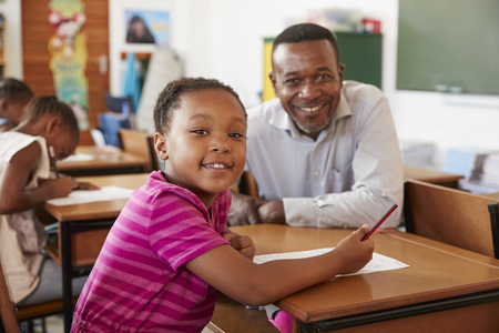 Black teacher and elementary school girl smiling to camera Stok Fotoğraf