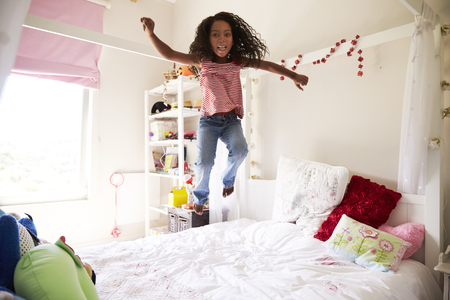 寝室のベッドの上で楽しいジャンプを持っている若い女の子
