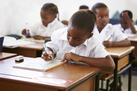 Schulmädchen, das an ihrem Schreibtisch in der Volksschulestunde schreibt Standard-Bild - 85280636