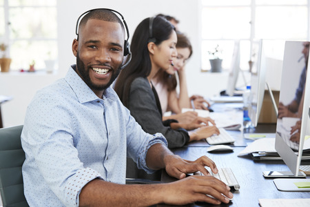 Young black man with headset on smiling to camera in office 스톡 콘텐츠