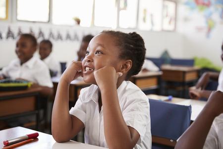 Chica escuchando durante una lección en una escuela primaria Foto de archivo - 85280654