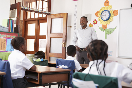Teacher welcomes kids sitting in elementary school class