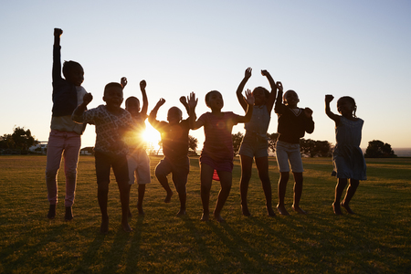 Silhouetted school kids jumping outdoors at sunset
