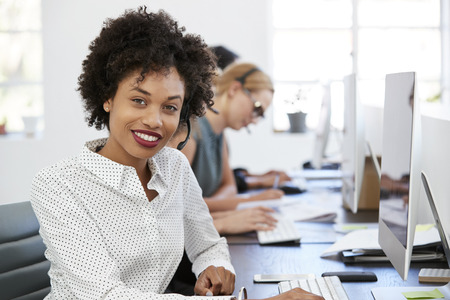 Young black woman with headset smiling to camera in office