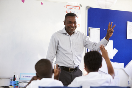 Teacher showing hand in front of an elementary school class