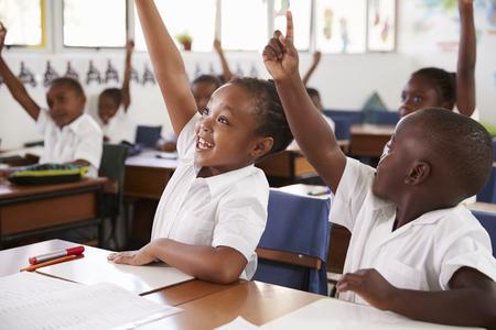 Enfants, levant les mains au cours de la leçon de l'école primaire, gros plan Banque d'images - 85280341