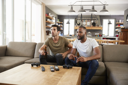 Two Male Friends Sit On Sofa And Watch Sports On Television Stok Fotoğraf