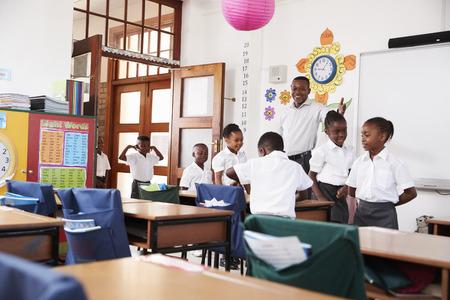 Teacher welcomes kids arriving to elementary school class