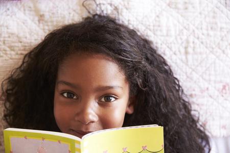 ベッドと読書本の上に横たわっている女の子の頭上の肖像