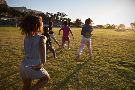 Elementary kids spelen voetbal in een veld, achteraanzicht Stockfoto
