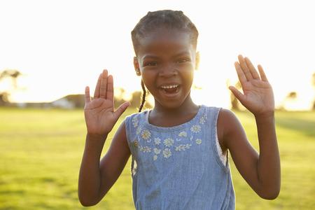 Portrait of African elementary school girl with hands raised Banco de Imagens