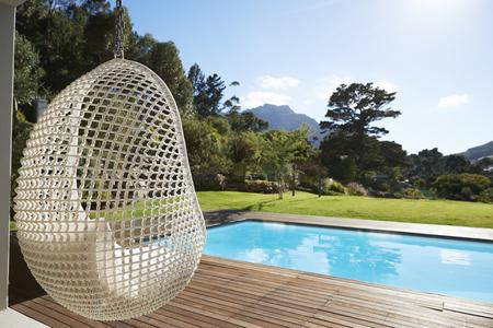 Suspended Seat Next To Decking Around Outdoor Swimming Pool Reklamní fotografie