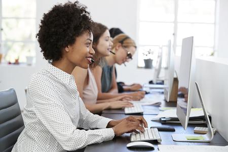 ヘッドセットとオフィスでコンピュータで働く若い黒人女性 写真素材